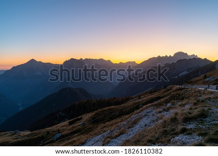 beautiful view over the Julian Alps with the sun setting over a beautiful mountain ridge on a cloudless day in autumn. Enjoying beautiful mountain vistas during twilight while traveling in Europe.  Royalty-Free Stock Photo #1826110382