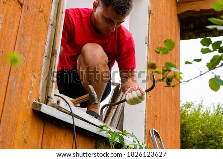 Replacement of a window and a window frame, dismantling of an old window in a private house in the countryside, the worker dismantles an old wooden window. Royalty-Free Stock Photo #1826123627