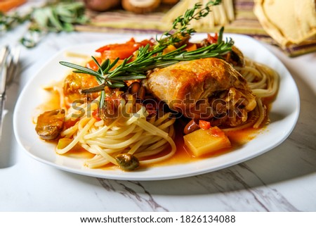 Italian chicken Cacciatore hunter's stew with spaghetti noodles and crusty bread Royalty-Free Stock Photo #1826134088