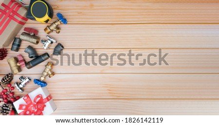 Christmas and New Year holiday decoration with construction tools on the wooden background top view. Plumber Christmas.