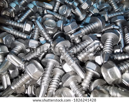 There are many metal self-tapping screws made of steel, self-tapping screw for metal, self-tapping screw for iron, chrome-plated self-tapping screw, scattered  screws as background Royalty-Free Stock Photo #1826241428