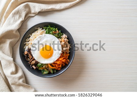 Bibimbap, Korean spicy salad with rice and fried egg - traditionally Korean food style Royalty-Free Stock Photo #1826329046