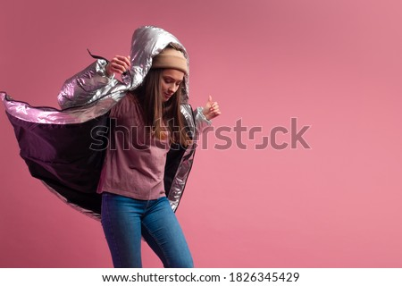 Trendy autumn and winter clothing, Studio shot on a pink background, copy space. A cool woman in a shiny silver down jacket and a knitted hat Royalty-Free Stock Photo #1826345429
