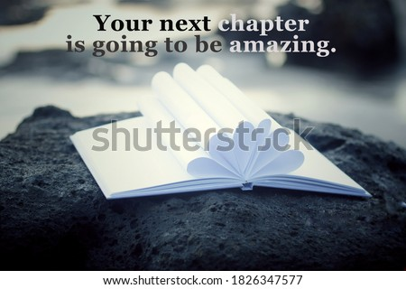 Inspirational motivational quote - Your next chapter is going to be amazing. With open book page and white paper pages flower shape decoration on a sea rock outdoor. White bokeh light background.
