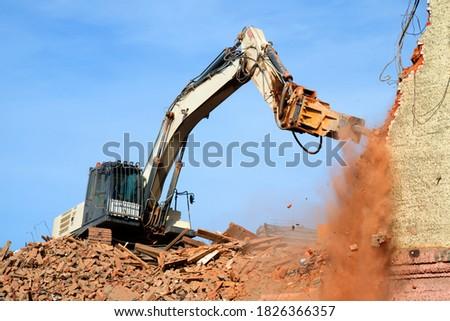 excavator demolishing a brick building. Machinery Demolishing Building #1826366357