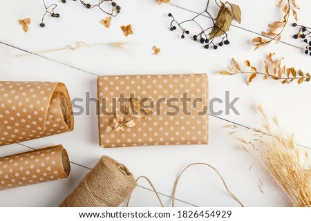 Packing autumn present in decorarive paper cover for delivery, shipping service. Craft present gift box on autumn background. Autumn birthday present. Fall leaves decor. Celebration thanksgiving day Royalty-Free Stock Photo #1826454929