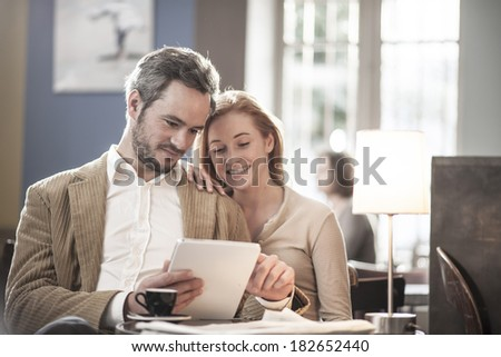 cheerful couple sitting in a cafe and using a digital tablet #182652440