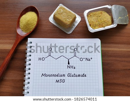 Structural chemical formula of monosodium glutamate (or MSG) with spoonful of a yellow, dry, seasoning spice mix and bouillon cubes. MSG is used in cooking as a flavor enhancer in many food.
