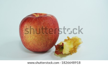 A red apple and an apple core are placed side by side. The back side is a white scene throughout the picture.