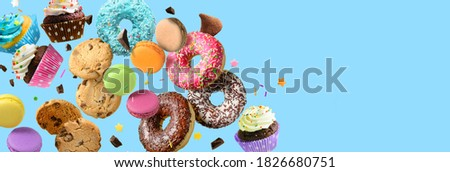 Cakes, sweets, confectionery collage background. Donuts, cookies cupcakes macaroons flying over blue background Royalty-Free Stock Photo #1826680751