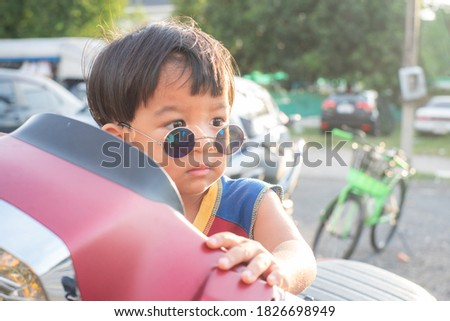 Little smart boy wear sunglasses sitting on vintage scooter motorcycle outdoor portrait Royalty-Free Stock Photo #1826698949