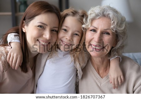 Head shot portrait smiling pretty little girl hugging young mother and mature grandmother, three generations of women looking at camera, posing for family photo, sitting on couch at home