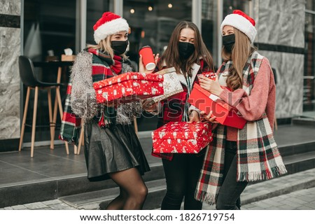 Three portrait of young happy women in red Christmas clothes, medical masks, hats and gifts walking in the city and shopping in quarantine. New year, boxes, girlfriends, shop, coronavirus, pandemic Royalty-Free Stock Photo #1826719754