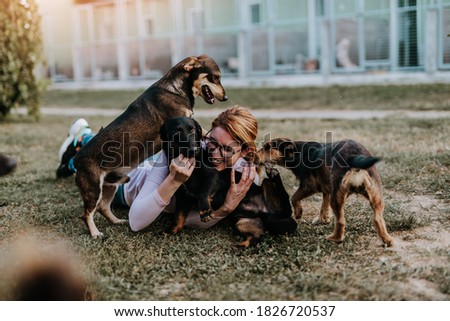 Young adult woman holding adorable dog in animal shelter. Royalty-Free Stock Photo #1826720537