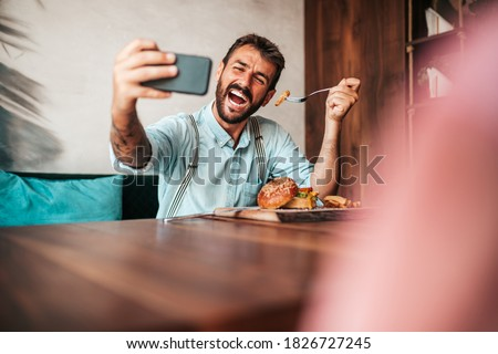 Handsome middle age man sitting in restaurant and enjoying in delicious burger. He is happy, smiled and using his smart phone for food photography shots. Royalty-Free Stock Photo #1826727245