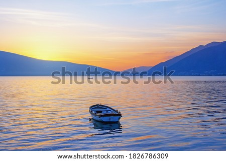 Beautiful winter Mediterranean landscape.  Sunset with fishing boat on the water. Montenegro, Adriatic Sea, Kotor Bay Royalty-Free Stock Photo #1826786309