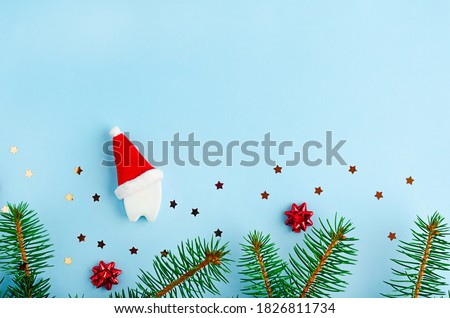 medical dental christmas on blue background with fir branches, creative toy tooth in red santa hat, copy space, place for text