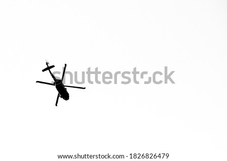 Silhouette helicopter flying on a black background.