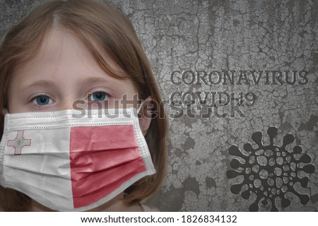 Little girl in medical mask with flag of malta stands near the old vintage wall with text coronavirus, covid, and virus picture. Stop virus