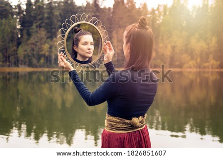 Autumn bohemian photo of a woman with long hair holding a round golden mirror with reflection of her face. Forest lake on the background. High quality stock photo.