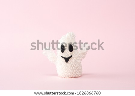 White Halloween ghost on a pink background. Minimal holiday concept.