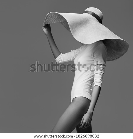 A graceful woman posing with a large wide-brimmed hat. Black and white image. Royalty-Free Stock Photo #1826898032