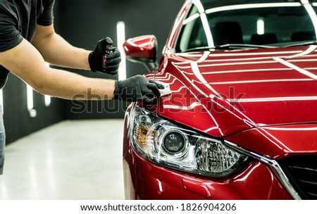 Car service worker applying nano coating on a car detail. Royalty-Free Stock Photo #1826904206