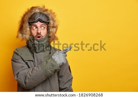 Stunned Caucasian man in winter clothes points away on blank space with surprised expression goes skiing during cold day wears jacket and gloves enjoys chilly weather isolated on yellow background Royalty-Free Stock Photo #1826908268