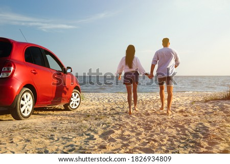 Lovely couple running on sandy beach. Summer trip Royalty-Free Stock Photo #1826934809