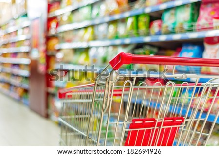 Supermarket interior, empty red shopping cart. Royalty-Free Stock Photo #182694926