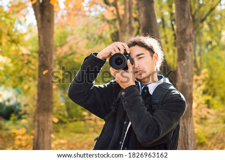 Amateur photographer with dark hair in black coat shooting in the park in autumn. Young man taking photos of fall landscapes in october.