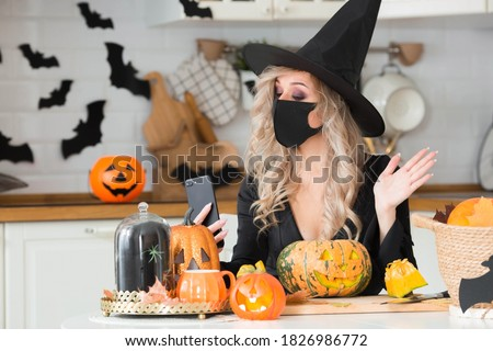 Happy Halloween. Online greetings. A woman wearing a black medical mask and a witch costume uses a mobile phone to make video calls to friends and parents. Royalty-Free Stock Photo #1826986772