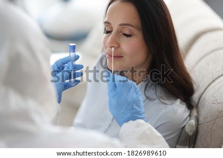 Doctor laboratory assistant in protective suit takes swab from nose of sick patient at home. Laboratory tests for coronavirus concept. #1826989610