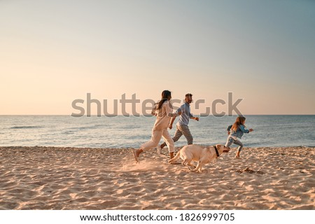 Happy family concept. Young attractive mother, handsome father and their little cute daughter having fun together on the beach and running with dog. Royalty-Free Stock Photo #1826999705
