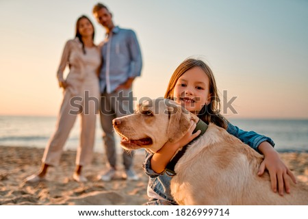 Happy family concept. Young attractive mother, handsome father and their little cute daughter standing together on the beach with dog. Royalty-Free Stock Photo #1826999714