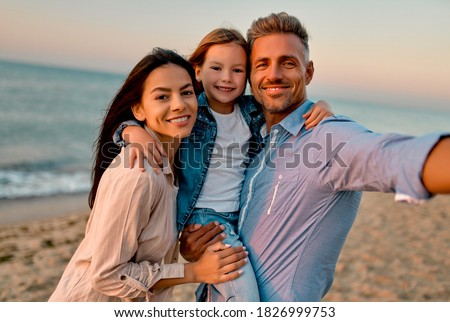 Happy family concept. Young attractive mother, handsome father and their little cute daughter standing together on the beach and making selfie. Royalty-Free Stock Photo #1826999753