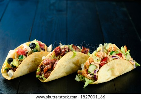 Three Mexican tacos with beef and vegetables on wooden dark background. Mexican dish with sauces guacamole and salsa three mexican pork carnitas tacos flat lay set composition with copy space.
