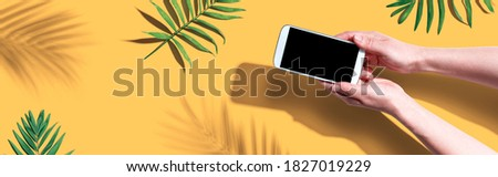 Smartphone with tropical palm leaves and shadow - flat lay Royalty-Free Stock Photo #1827019229