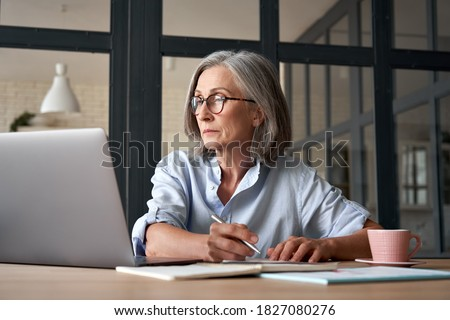 Serious mature older adult woman watching training webinar on laptop working from home or in office. 60s middle aged businesswoman taking notes while using computer technology sitting at table. Royalty-Free Stock Photo #1827080276