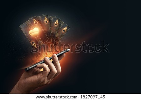 In the hands of a smartphone with playing cards, black-gold background. Concept of online gambling, online casino. Copy space Royalty-Free Stock Photo #1827097145