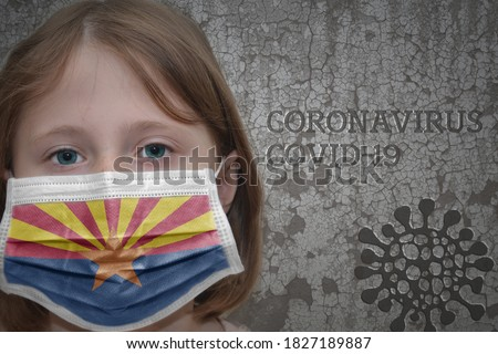 Little girl in medical mask with arizona state flag stands near the old vintage wall with text coronavirus, covid, and virus picture. Stop virus