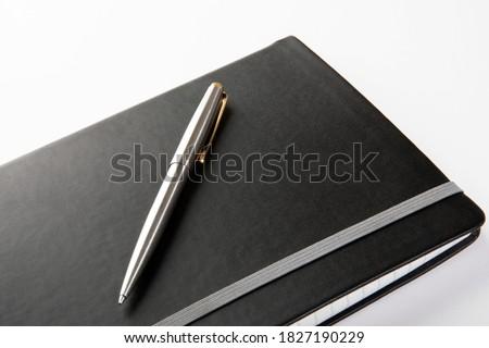 Custom silver ballpoint pen on modern black journal on a white background.