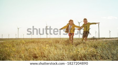 Little girl and boy are running in front of windmills. Renewable energies and sustainable resources - wind mills. children playing with the wind near a wind turbine Royalty-Free Stock Photo #1827204890