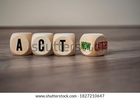 Cubes dice with act now and act later on wooden background Royalty-Free Stock Photo #1827210647