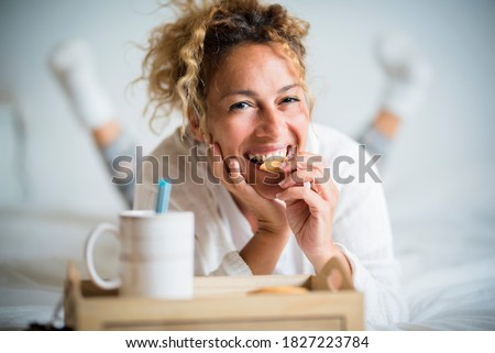 Portrait of adult beautiful woman eating cookie in morning breakfast in the bedroom - home or hotel wake up day with pretty female people lay down with biscuit and tea - cheerful and happy face lady Royalty-Free Stock Photo #1827223784