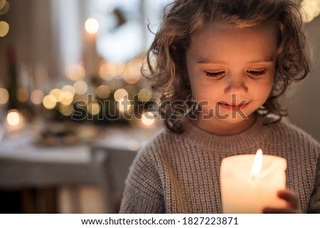 Cheerful small girl indoors at home at Christmas, holding candle. Royalty-Free Stock Photo #1827223871