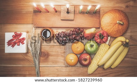 Kwanzaa holiday concept with decorate seven candles red, black and green, gift box, pumpkin,corn and fruit on wooden desk.