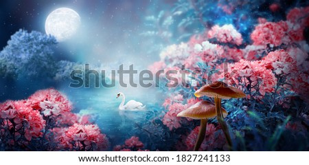 Fantasy magical enchanted fairy tale landscape with swan swimming in lake, fabulous fairytale blooming pink rose flower garden and mushrooms on mysterious blue background and glowing moon ray in night Royalty-Free Stock Photo #1827241133