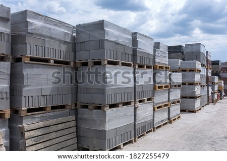 Industrial production of building cement pressed materials. High quality hollow concrete block or cement brick and paving stones. Finished products on pallets packed in film are waiting to be shipped. Royalty-Free Stock Photo #1827255479