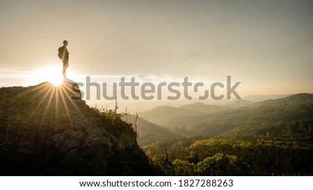 Hiker, Backpacking on top of a mountain cliff. Dreamy Dramatic Sunset Composite. Landscape taken in Lusatian mountains with wide panorama. Concept: Adventure, Art, Travel, Hike, Outdoors and Sports.  Royalty-Free Stock Photo #1827288263